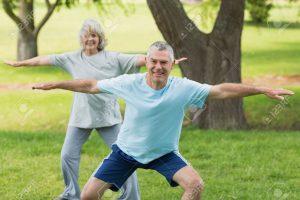 זוג מבוגרים עושים כושר על הדשא