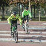 2 גברים רכובים על אופניים אחד אחרי השני